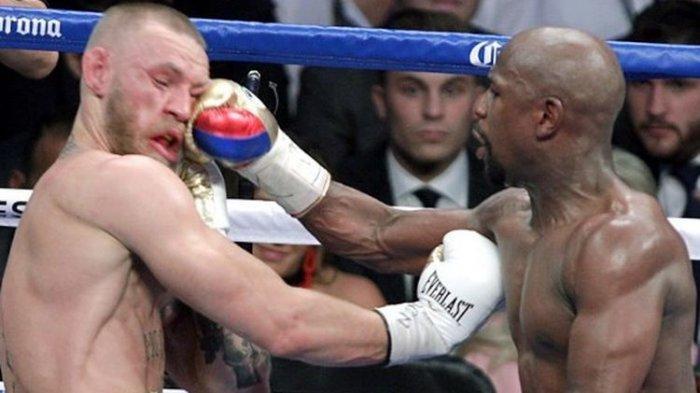 Floyd Mayweather Jr melepaskan pukulan ke arah wajah Conor McGregor pada pertarungan yang bertajuk The Money Fight yang digelar di T-Mobile Arena, Paradise, Nevada, Amerika Serikat, 26 Agustus 2017.