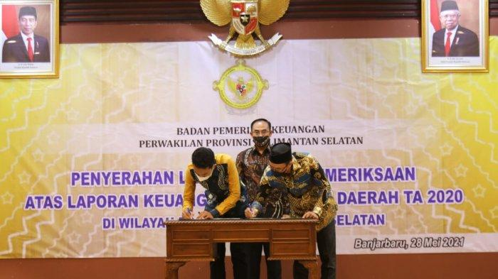 Bupati Banjar Saidi Mansyur menandatangani berita acara menerima dokumen Laporan Hasil Pemeriksaan BPK Perwakilan Kalsel atas Laporan Keuangan Pemerintah Daerah Tahun 2020 di Kota Banjarbaru, Jumat (28/5/2021).