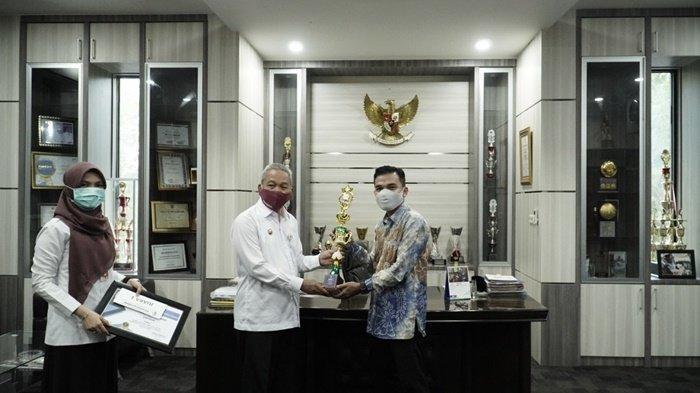 Bupati HA Chainrasyah menyerahkan piala kepada pemenang pembuat logo, saat di kantornya, Kota Barabai, Kabupaten Hulu Sungai Tengah (HST), Provinsi Kalimantan Selatan, Rabu (16/12/2020).