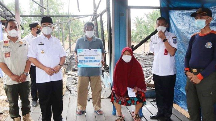 Bupati Drs H Achmad Fikry bersama para korban kebakaran, setelah penyerahan bantuan, di Desa Sungai Kupang RT 07 Kecamatan Kandangan, Kota Kandangan, Kabupaten Hulu Sungai Selatan (HSS), Provinsi Kalimantan Selatan, Rabu (21/7/2021).