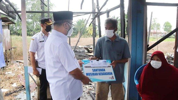 Bupati Drs H Achmad Fikry menyerahkan bantuan kepada kroban kebakaran di Desa Sungai Kupang RT 07 Kecamatan Kandangan, Kota Kandangan, Kabupaten Hulu Sungai Selatan (HSS), Provinsi Kalimantan Selatan, Rabu (21/7/2021).