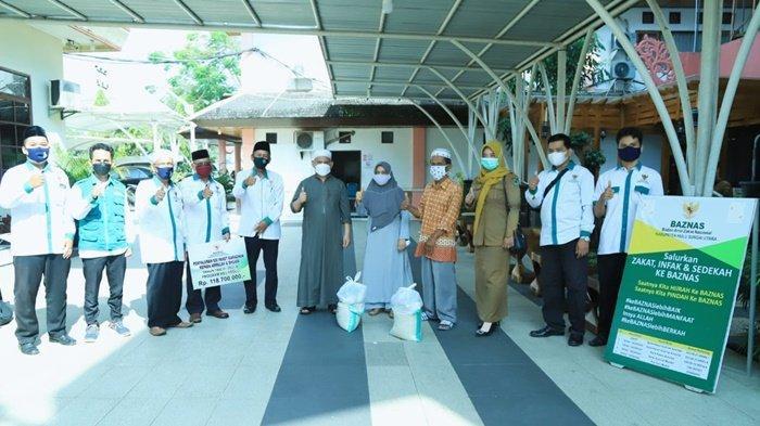 Bupati Hulu Sungai Utara (HSU), H Abdul Wahid HK (enam dari kanan), foto bersama pengurus Baznas Kabupaten HSU dan warga penerima bantuan.