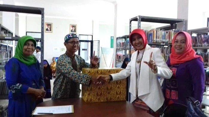 drg Yasna Khairina (baju putih), Kepala Dinas Perpustakaan dan Kearsipan (Dispersip) Kabupaten Banjar, bersama staf dan pengunjung perpusatakaan.