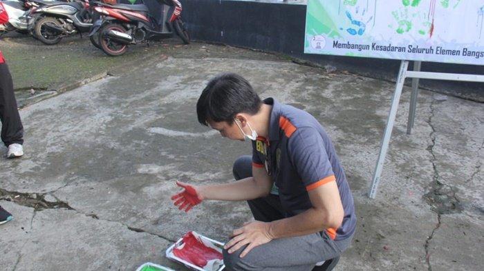 Telapak tangan bercat warna, sebelum ditempelkan di dinding dukungan anti korupsi di Taman Pahlawan, Kota Amuntai, Kabupaten Hulu Sungai Utara (HSU), Kalimantan Selatan.