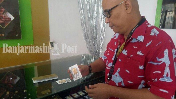 Vice President PT Pegadaian area Kalselteng, Ade Harsono, memperlihatkan emas batangan yang tersedia di Pegadaian.