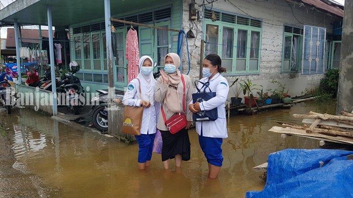 Kader Posyandu Teluk Selong Kabupaten Banjar Cari Balita untuk Ditimbang