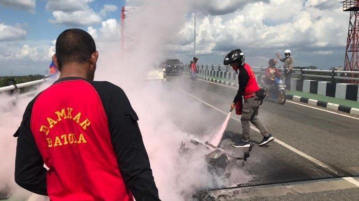 Anggota Damkar Barito Kuala berupaya memadamkan kendaraan Boy yang terbakar di Jembatan Rumpiang, Marabahan
