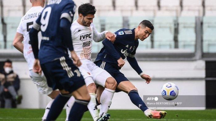Penyerang Juventus Cristiano Ronaldo (kanan) diapit dua pemain Benevento dalam pertandingan sepak bola Liga Italia Serie A, Mingg 21 Maret 2021 di Stadion Allianz di Kota Turin.