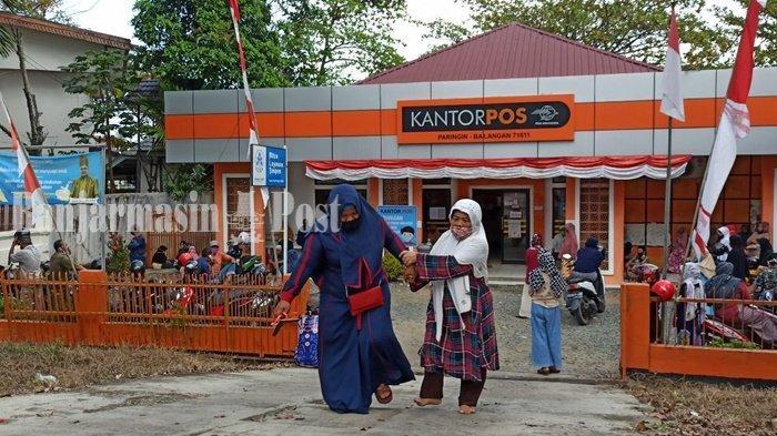 ILUSTRASI - Masriah, warga Sungai Ketapi berjalan dibantu anaknya keluar dari Kantor Pos Paringin, Kabupaten Balangan, Kalimantan Selatan, setelah menerima Bantuan Sosial Tunai (BST), Selasa (25/8/2020).