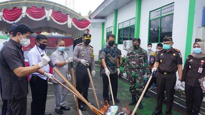 Ketua DPRD Barito Kuala, Saleh (enam dari kanan), bersama pimpinan forkopimda dan yang mewakili, membakar barang bukti kejahatan di Kejaksaan Negeri Barito Kuala, Kota Marabahan, Kalimantan Selatan, Rabu (24/3/2021).