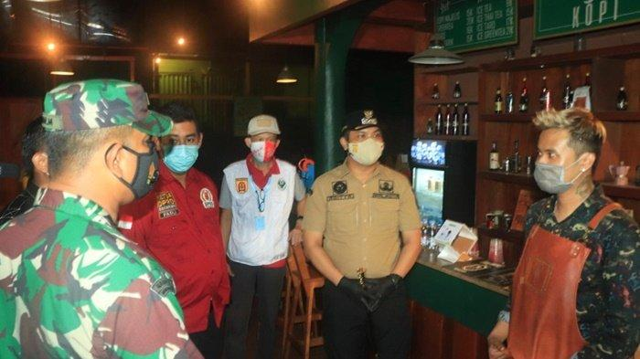 Ketua DPRD Kota Banjarbaru, Fadliansyah SH MH (baju merah), dan Wali Kota Banjarbaru, HM Aditya Mufti Ariffin, saat Operasi Yustisi menanyai pengelola salah satu kafe, Sabtu (13/3/2021) malam.