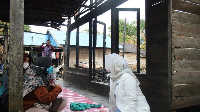 Ketua Tim Penggerak PKK Kabupaten Banjar, Hj Nurgita Tiyas Saidi Mansyur, tak sungkan duduk di rumah bekas terbakar di Desa Kalampayan Ulu, Kecamatan Astambul, Kalimantan Selatan, Kamis (6/5/2021).