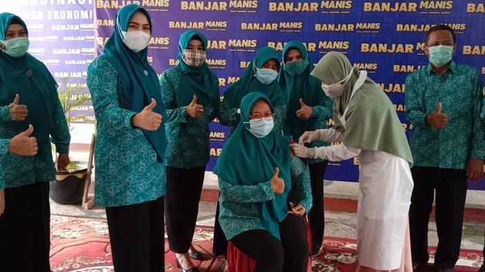 Ketua TP PKK Kabupaten Banjar, Hj Nurgita Tyas Saidi (dua dari kiri), acung jempol pada anggotanya yang divaksin Covid-19 di Pendopo Sultan Adam Martapura, Kalimantan Selatan, Rabu (31/3/2021).