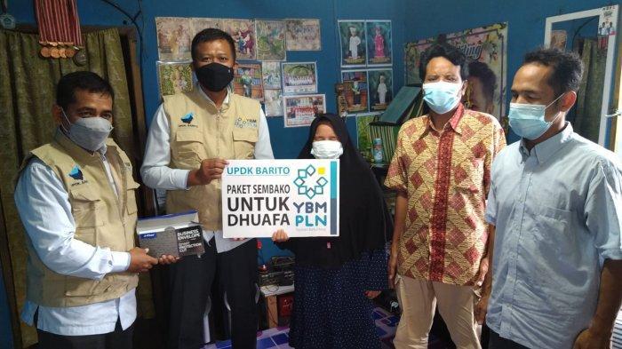 Manager PLN UPDK Barito, Nazrul Very Andhi, menyerahkan bantuan kepada perwakilan tunanetra