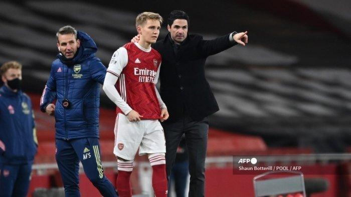 Gelandang Martin Odegaard (kiri) mendapat instruksi dari manajer Arsenal Mikel Arteta (kanan) saat ia masuk sebagai pemain pengganti pada pertandingan sepak bola Liga Inggris Premier League antara Arsenal vs Manchester United di Stadion Emirates di London pada 30 Januari 2021.