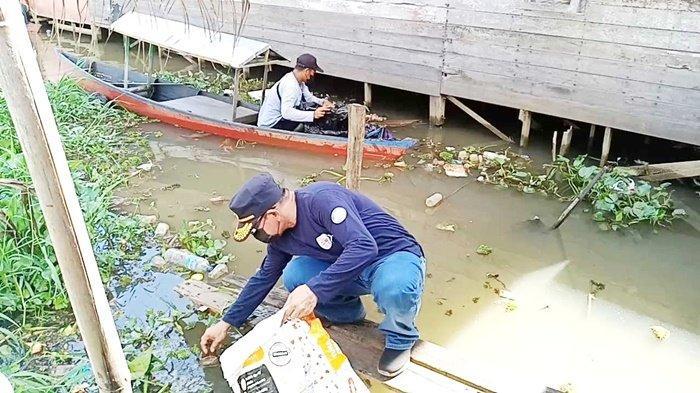 Memungut sampah pada Hari Bersih-bersih Sedunia atau World Cleanup Day (WCD) sekaligus Kick Off Program Sungai Martapura Bersih, Unggul dan Asri (Bungas), di Lokbaintan, Kecamatan Sungai Tabuk, Kabupaten Banjar, Provinsi Kalimantan Selatan, Sabtu (18/9/2021).