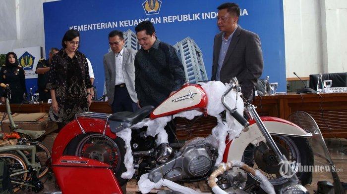 Menteri Keuangan Sri Mulyani bersama Menteri BUMN Erick Thohir menunjukkan barang bukti motor Harley Davidson saat konferensi pers terkait penyelundupan motor Harlery Davidson dan sepeda Brompton menggunakan pesawat baru milik Garuda Indonesia di Kementerian Keuangan, Jakarta, Kamis (5/12/2019).