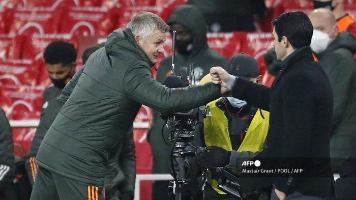 Manajer Manchester United asal Norwegia, Ole Gunnar Solskjaer (kiri) dan manajer Arsenal asal Spanyol Mikel Arteta (kanan) melakukan pukulan tinju setelah kedua tim berlaga pada lanjutan Liga Inggris Premier League pekan 20 di Emirates Stadium, London pada 30 Januari 2021. Pertandingan berakhir 0- 0.