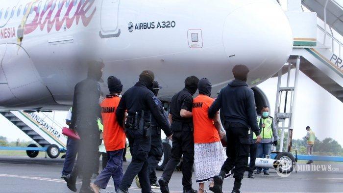 Pasukan Detasemen Khusus (Densus) 88 Antiteror Mabes Polri menggiring tahanan tersangka teroris menuju ke dalam pesawat di Bandara Radin Inten, Brantiraya, Lampung Selatan, Lampung, Rabu (16/12/2020). Sebanyak 23 tahanan tersangka terorisme yang ditahan di Mako Brimob Polda Lampung, di antaranya Zulkarnain alias Arif Sunarso yang terlibat dalam kasus teror Bom Bali I pada 2002 dan Taufik Bulaga alias Upik Lawanga dipindahkan ke Jakarta menggunakan pesawat terbang. Tribun Lampung/Deni Saputra
