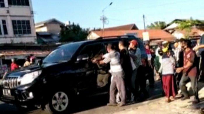 Pengemudi mobil hitam itu membagikan sejumlah uang, nominal Rp 50 ribu secara acak di kawasan terminal Km 6 Banjarmasin