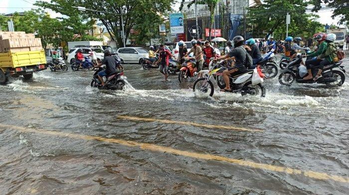 Pengendara menghadapi kondisi banjir