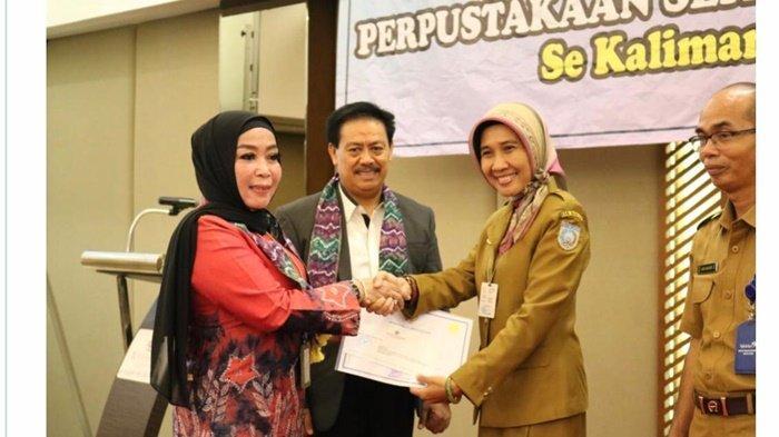 Penyerahan sertifikat Akreditasi dengan nilai A yang diterima drg Yasna Khairina (dua dari kanan), Kepala Dinas Perpustakaan dan Kearsipan (Dispersip) Kabupaten Banjar.