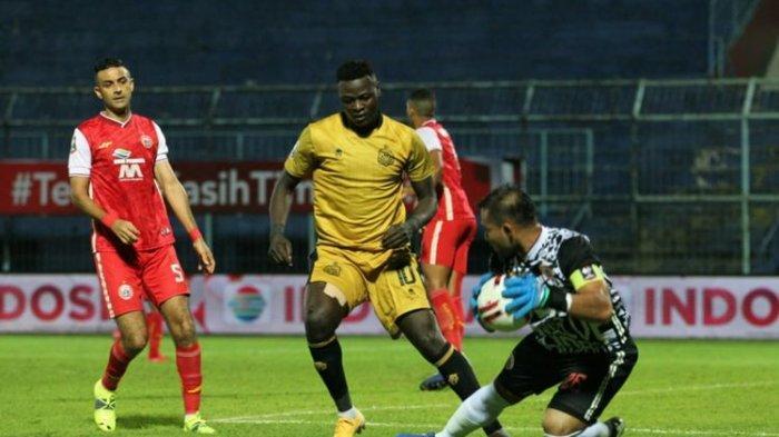 Penyerang Bhayangkara FC, Ezechiel Ndouassel, berduel dengan kiper Persija, Andritany Ardhiyasa, pada laga Persija Jakarta vs Bhayangkara Solo FC di Grup B Piala Menpora 2021 di Stadion Kanjuruhan, Malang, Jawa Timur pada Rabu (31/3/2021) sore hari WIB.