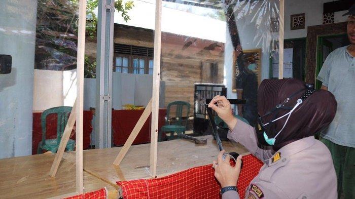 Perwira Polres Banjar mencoba menandai untuk lubang interaksi pada pembatas panitia pemungutan suara pilkades dengan pemilh di sebuah TPS di salah satu desa di wilayah Kecamatan Karang Intan, Kalimantan Selatan, Minggu (23/5/2021).