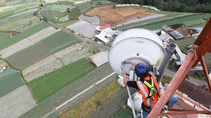 Petugas XL melakukan cek Keandalan sistem di tower BTS XL Axiata.