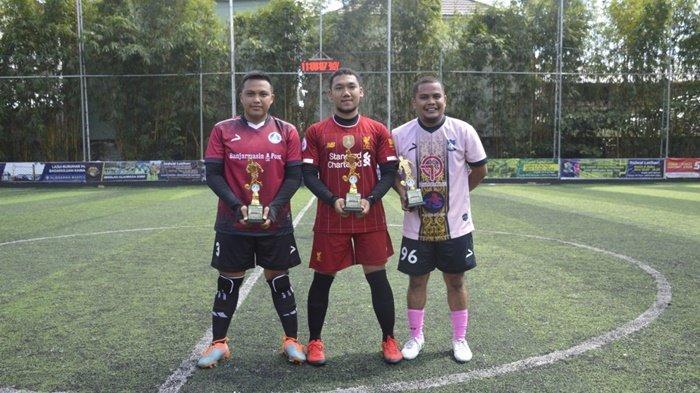 Pimpinan tiga tim, BPost FC, Alumni SMP 9 Banjarmasin dan Bigreds Banjarmasin, memegang piala setelah mengikuti ajang trofeo yang dihelat di Upik Mini Soccer, Banjarmasin, Kalimantan Selatan, Minggu (25/7/2021).