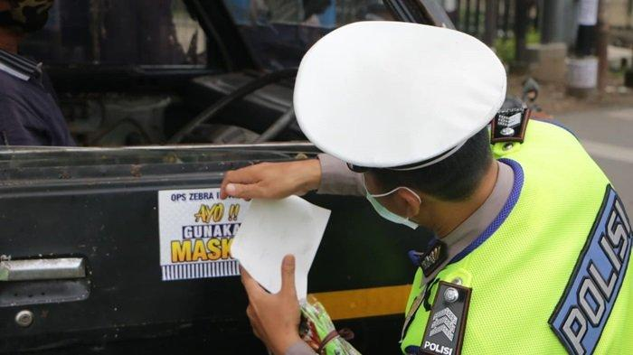 Petugas Ditlantas Polda Kalsel tempelkan stiker ayo gunakan masker