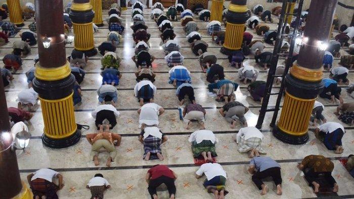 Umat Islam melaksanakan shalat Jumat di Masjid Agung Baitul Hakim, Kota Madiun, Jawa Timur, Jumat (24/4/2020). Shalat Jumat hari pertama Ramadhan 1441 H di masjid tersebut diikuti ratusan umat Islam dengan menerapkan physical distancing, mengenakan masker dan melewati bilik penyemprotan cairan disinfektan, serta dilakukan penyemprotan cairan disinfektan di masjid guna mencegah penyebaran COVID-19. ANTARA FOTO/Siswowidodo/pras.