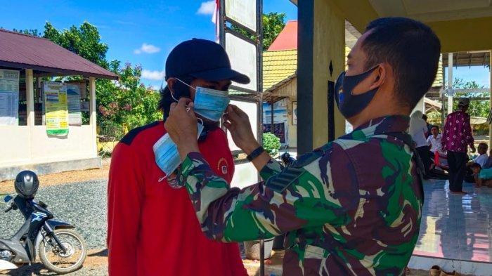 Serma Ibnu menyapa dan menegus warga yang tak mengenakan masker. Sekaligus ia memberikan masker gratis, kemarin.