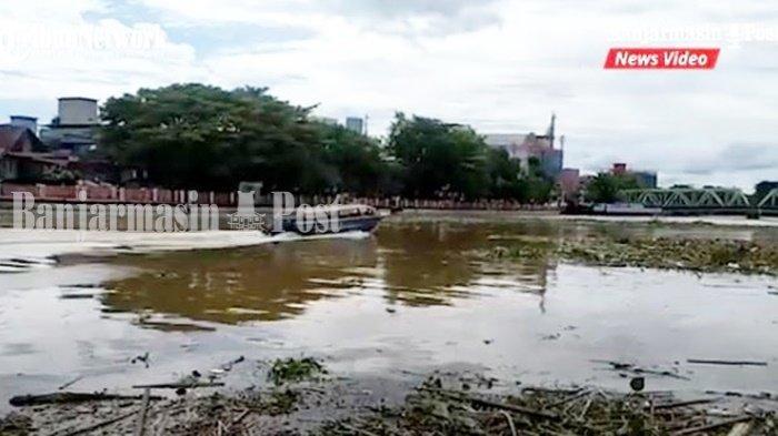 Speed boat melintas di antara sampah di Sungai Martapura, Kota Banjarmasin, Provinsi Kalimantan Selatan, Minggu (7/3/2021).
