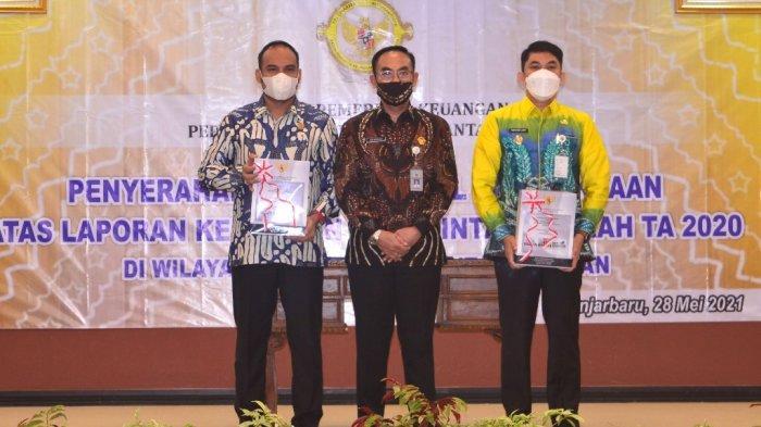 Ketua DPRD Syairi Mukhlis (kiri), Wakil Bupati Kotabaru Andi Rudi Latif (kanan) memperlihatkan dokumen terkait penyerahan LHP, Kabupaten Kotabaru kembali meraih predikat opini WTP diraih berturut-turut enam kali