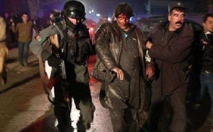 Pasukan polisi Afganistan membantu seorang pria yang terluka di sebuah lokasi ledakan bom bunuh di di Kabul, Jumat (17/1/2014).
