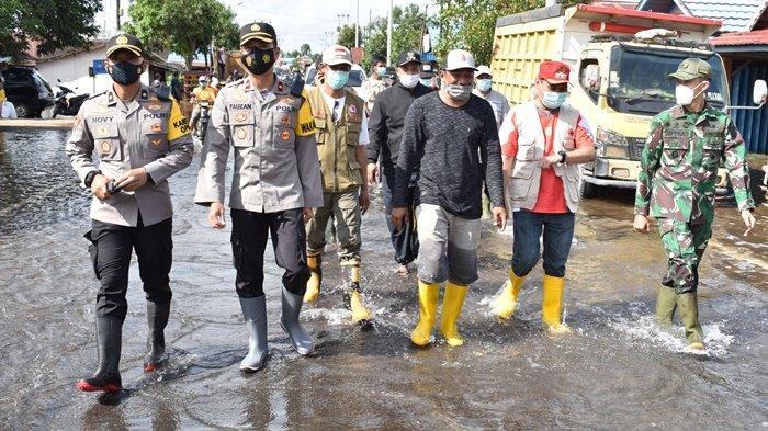Wakil Kepala Polres Tanah Laut (Tala), Kompol Fauzan Arianto SH SIK MH, bersama Wakil Bupati, Abdi Rahman (kedua kanan, kaus merah), serta forkopimda dan stakeholder meninjau lokasi Banjir, kemarin.