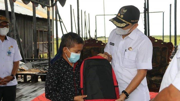 Wakil Bupati Syamsuri Arsyad menyerahkan perlengkapan sekolah kepad seorang anak yang rumahnya terbakar di Desa Bajayau Tengah RT 02 RW 02, Kecamatan Daha Barat, Kabupaten Hulu Sungai Selatan (HSS), Provinsi Kalimantan Selatan, Rabu (19/5/2021).