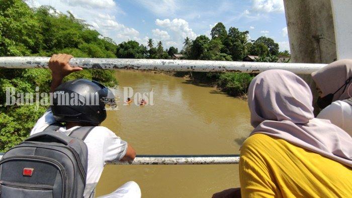 Warga dari Jembatan 1 Juli Hikun menyaksikan petugas melakukan pencarian seorang perempuan diduga tenggelam di Sungai Tabalong, kawasan perbatasan Kelurahan Hikun, Kecamatan Tanjung dan Desa Kapar Kecamatan Murung Pudak, Kabupaten Tabalong, Provinsi Kalimantan Selatan, Senin (19/7/2021)