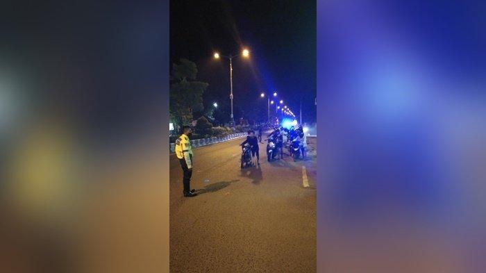 Petugas mengawasi sekelompok pengendara mendorong motornya dari kawasan Lapangan Murjani menuju polres di Kota Banjarbaru, Kalimantan Selatan, Minggu (18/4/2021) dini hari.