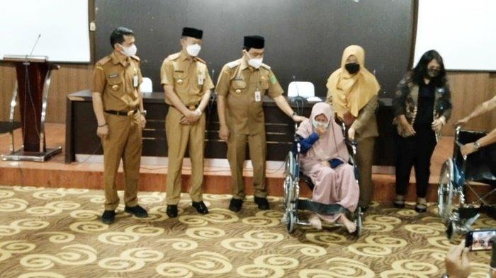 Winda Andriani, pensiunan dari Puskesmas Simpangempat, Kabupaten Tanah Bumbu (Tanbu), Kalimantan Selatan, menangis saat mendapatkan bantuan kursi roda, Senin (26/4/2021).