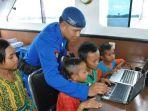 anggota-ditpolair-polda-kalsel-mengajari-anak-anak-mengoperasikan-laptop_20170309_201001.jpg