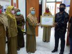 anggota-komisi-ii-dprd-setempat-yazid-fahmi-saat-menyerahkan-alat-pelindung-diri-apd.jpg