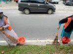 dua-warga-menyapu-jalan-setelah-terjaring-operasi-yustisi-di-jalan-murjani-palangkaraya.jpg