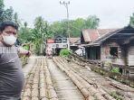 kepala-desa-banjang-yusni-menunjukkan-jembatan-batang-pohon-kelapa-hsu-selasa-01092021.jpg