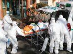 para-pekerja-medis-dilengkapi-pakaian-pelindung-memindahkan-seorang-pasien-diduga.jpg