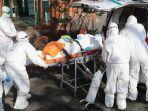 para-pekerja-medis-yang-mengenakan-alat-pelindung-memindahkan-seorang-tersangka-pasien-virus-korona.jpg