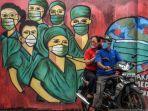pengendara-motor-melintas-di-depan-mural-tentang-pandemi-virus-corona.jpg