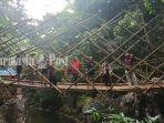 pengunjung-di-jembatan-gantung-berlatar-belakang-pemandian-batu-badinding-8102020.jpg