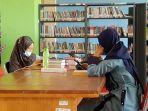 pengunjung-membaca-buku-secara-santai-di-ruang-baca-di-dispusip-tala-yang-lapang-dan-nyaman.jpg